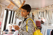 Black woman riding train and holding cell phone - Stock Image - CXX6DW