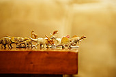 Toy dinosaurs rush off edge of table - Stock Image - C00DE2