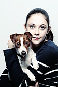 young girl holding a jack russell puppy dog - Stock Image - A1BXE7