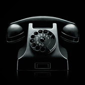 old vintage rotary dial black telephone photographed on very moody dark black background - Stock Image - DWDNA4