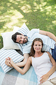 Couple relaxing on picnic blanket - Stock Image - DRCCNM