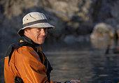 Man sitting on still sea - Stock Image - CR21NH