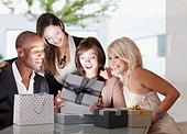 Friends watching woman open gift - Stock Image - C4M36M