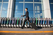 Traveler walking fast next to row of luggage carts at airport - Stock Image - D790G6