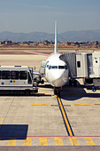 Passenger airplane being serviced at the gate - Stock Image - CC1MDM
