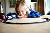 Girl playing with a toy train - Stock Image - BRMT9A