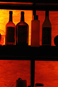 Silhouette of Back Lit Bottles of Liquor on Shelves with Copy Space - Stock Image - AJXMNX