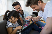 Homosexual couple and daughter using digital tablet - Stock Image - ERBP7F