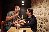 Two men having lunch in restaurant, one man showing the other his smartphone screen - Stock Image - EKHX4Y