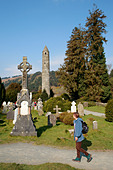 round tower and tombstones at Glendalough in County Wicklow in Ireland - Stock Image - A862KP