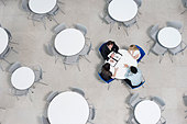 Overhead view of informal business meeting at table of staff canteen - Stock Image - B07WF5