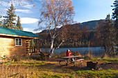 Woman enjoys looking at views through binoculars while at a picnic table, Byers Lake Public Use Cabin, Denali State Park, Alaska - Stock Image - C53G9D