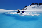 Two Hikers Drift on Iceberg in Melt Pond Composite AK SE Summer - Stock Image - ADH4BB