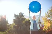 Senior woman holding fitness ball in park - Stock Image - DFEK20