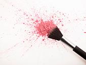 Makeup brush and pink blush powder splatter - Stock Image - D2XJ43