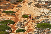 Female backpacker walking across rough ground near Cape Greco, Cyprus. - Stock Image - EFJCD2