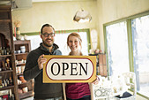 Two people standing in a store full of antique objects a couple running a business Holding a large sign saying OPEN - Stock Image - DT1J19