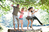 Four young people jumping from a log - Stock Image - BGMN18