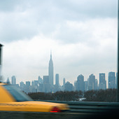 Urban Scene of a Yellow Taxi Cab and the New York City Skyline including the Empire State Building and has Copy Space - Stock Image - APPH4P
