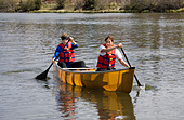 High school girls paddle a kevlar canoe on the Deschutes River in Bend, Oregon - Stock Image - BKR9GN