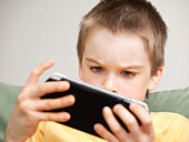 Boy playing game console - Stock Image - DC44W9