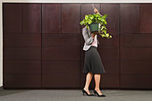 Business woman carrying plant - Stock Image - A8A3H2