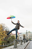 Full length of businessman with umbrella balancing on bollard outdoors - Stock Image - E08912