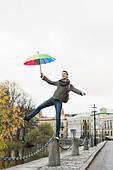 Full length of businessman with umbrella balancing on bollard outdoors - Stock Image - E08912