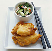 Fried fish in batter with vegetable salad - Stock Image - BJK2B4