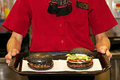 """Tokyo, Japan. 19th Sep, 2014. A woman shows two kinds of """"kuro burger"""" or """"black burger"""" at Burger King restaurant on September 19, 2014 in Tokyo, Japan. Burger King launches to its menu two kinds of black burgers """"Kuro Diamond"""" and """"Kuro Pearl"""" which contains black buns and black cheese made from bamboo charcoal, garlic sauce made with squid ink and beef patties made with black pepper all in black color starting on Friday, September 19 for a limit period. © Aflo Co. Ltd./Alamy Live News - Stock Image - E7JAD8"""