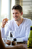 Portrait of a handsome guy holding a glass of wine at a restaurant - Stock Image - CP86BP