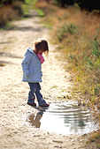 Girl dips her toe in a puddle - Stock Image - AEA2C9