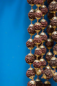 Close-up of japamala rudrasksha prayer beads against blue background - Stock Image - AYFAWE