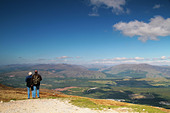 two people stood at the top of a mountain admiring the view - Stock Image - B219KY