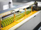 Close up of yellow ink in printing press - Stock Image - CRKDBA