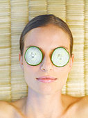 Woman relaxing with cucumber slices on her eyes - Stock Image - ACCDKG