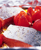 Salmon fillet with tomatoes on aluminium foil - Stock Image - BJJC65