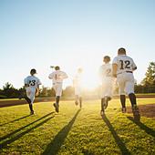 Baseball players (10-11) running on baseball diamond - Stock Image - BY3E09