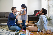 Playful homosexual couple and daughter in living room - Stock Image - ERBP8C