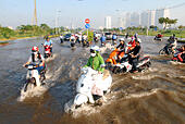 Ho Chi Minh City, Vietnam. 10th Oct, 2014. Citizens try to cross a flooded street caused by high tide in Ho Chi Minh City, Vietnam, Oct. 10, 2014. The high tide reached 1.58 meters at 5:00 a.m. Friday and may continue to rise, said the Southern Region Hydro-Meteorological Center of Vietnam. © VNA/Xinhua/Alamy Live News - Stock Image - E8M47T