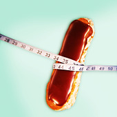a chocolate eclair with a tape measure around the middle - Stock Image - AB20G4