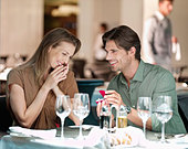 Man with engagement ring proposing to woman in restaurant - Stock Image - CWJPX2