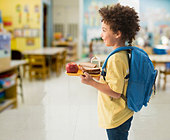 Mixed race boy having lunch at school - Stock Image - D93DGX