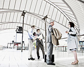 Business people waiting in train station - Stock Image - BN2E62
