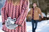 Man approaching woman with Christmas gift behind back - Stock Image - CWJM93