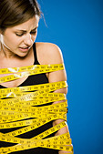 Woman wrapped in measuring tape - Stock Image - BJK6FN