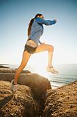 USA, California, San Diego, Woman jogging along sea coast - Stock Image - CFM4E6
