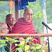 """Glastonbury Festival, Somerset, UK. 28th June 2015. His Holiness the 14th Dali Lama makes a joke as he celebrated his 80th year whilst addressing the Glastonbury Festival from the Peace Garden where a large crowd sang """"Happy Birthday to You"""". Security was tight during his visit where there were some demonstrators. © Tom Corban/Alamy Live News - Stock Image - EWKB38"""