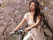 Young smiling Asian woman riding a bicycle in a park past blooming cherry trees - Stock Image - C4T3EN