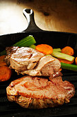 Wild boar steaks with vegetables in grill pan - Stock Image - BJPN0Y